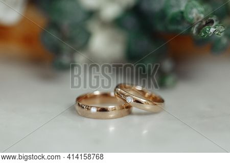 Wedding Day. Gold Wedding Rings On White Marble Stone, Details At The Wedding. Happy Day. Close-up.