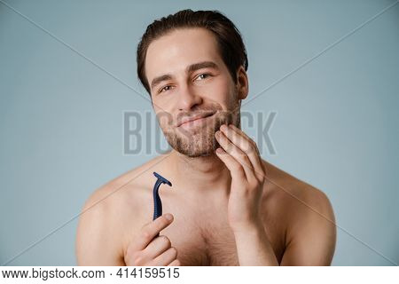 Happy mid aged shirtless man with stubble holding razor standing over blue wall