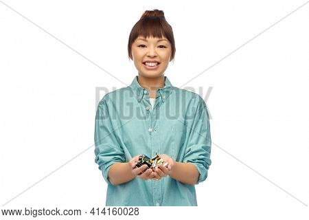 smiling young asian woman with alkaline batteries