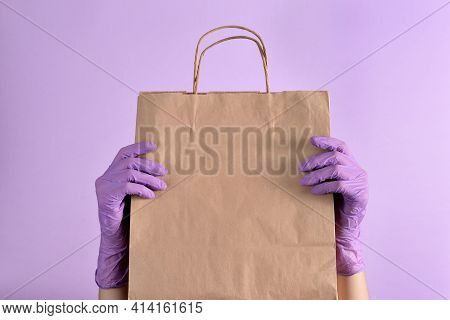 Women's Hands In Lilac Medical Gloves Hold A Paper Bag Of Food On An Isolated Purple Background. Rea