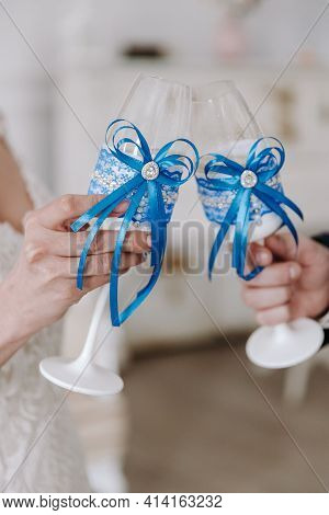 Wedding Day. Hands Of The Bride And Groom Are Holding Wedding Glasses With Champagne, Decorated In B