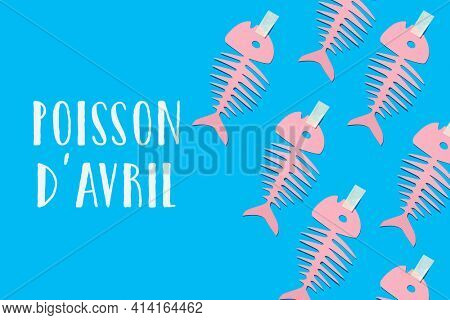 some homemade pink paper fishes and text fish of april written in french, the equivalent of april fools day in france, where it is popular to attach paper fishes to peoples backs as a prank
