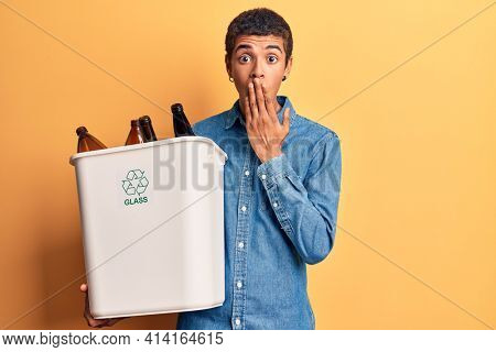 Young african amercian man holding recycling wastebasket with glass covering mouth with hand, shocked and afraid for mistake. surprised expression