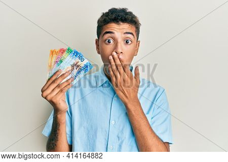 Young handsome african american man holding swiss franc banknotes covering mouth with hand, shocked and afraid for mistake. surprised expression
