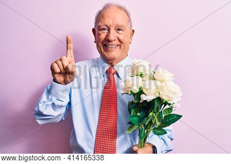 Senior grey-haired businessman wearing tie holding bouquet of flowers over pink background smiling with an idea or question pointing finger with happy face, number one