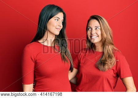 Hispanic family of mother and daughter wearing casual clothes over red background smiling looking to the side and staring away thinking.