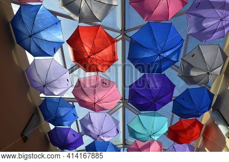 Low Angle View Of Colorful Umbrellas Hanging Outdoors.the Ceiling In The Store Is Decorated With Rai