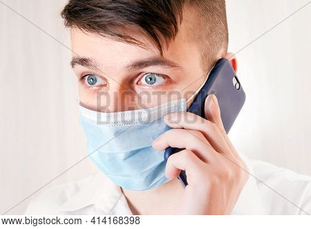 Shocked Young Man In Flu Mask With A Mobile Phone On The White Background Closeup
