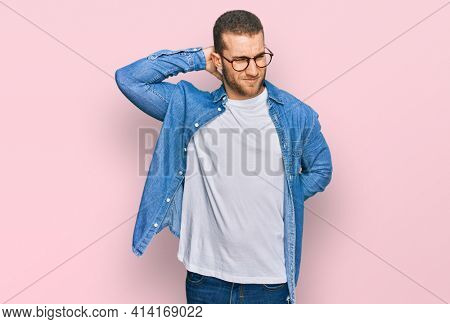 Young caucasian man wearing casual clothes suffering of neck ache injury, touching neck with hand, muscular pain