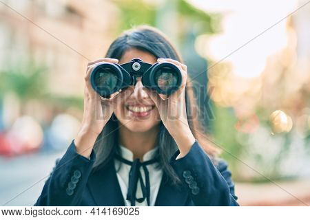 Young hispanic businesswoman looking for new opportunity using binoculars at the city.