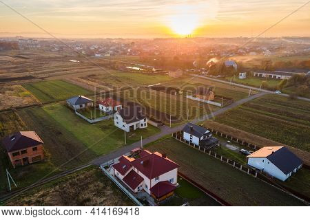 Aerial View Of Private Homes In Rural Suburban Area At Sunset.
