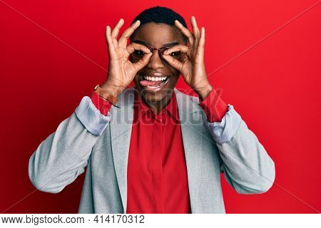 Young african american woman wearing business jacket and glasses doing ok gesture like binoculars sticking tongue out, eyes looking through fingers. crazy expression.