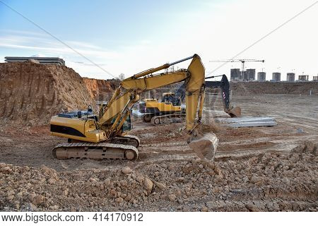 Excavator During Excavation At Construction Site. Backhoe On Foundation Work In Sand Pit. Groundwork