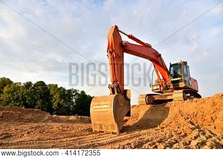 Excavator Dig Sand At The Open-pit. Heavy Machinery Working In The Mining Quarry. Digging And Excava