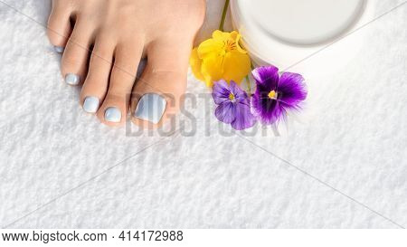 Female Bare Foot With Soft Blue Pedicure, A Violet And Yellow Pansy Flowers And A Cream Can On White
