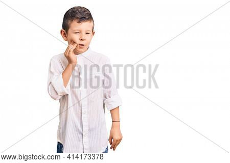 Cute blond kid wearing elegant shirt touching mouth with hand with painful expression because of toothache or dental illness on teeth. dentist