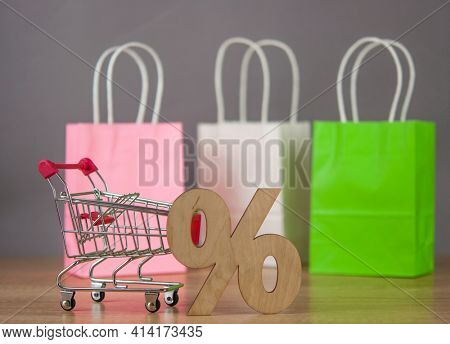 E-commerce online shopping idea concept. Trolley cart with colorful paper shopping bag on wooden table. Copy space.