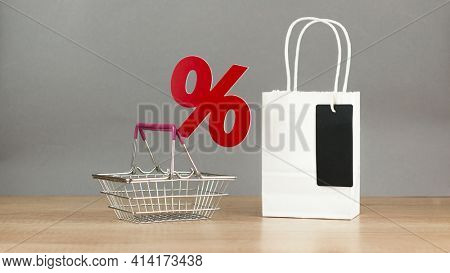 Shopping cart from the supermarket with sign percent over gray wall background. Shopping in the Mall, shop, shopping, a large selection.