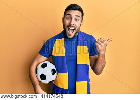 Young hispanic man football hooligan soccer ball pointing thumb up to the side smiling happy with open mouth
