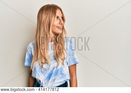 Beautiful blonde young woman wearing tye die tshirt looking to side, relax profile pose with natural face and confident smile.