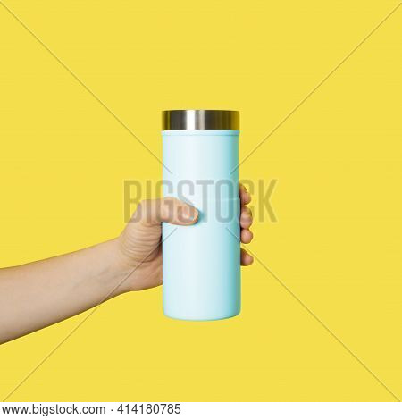 Hand Holds Travel Mug Isolated On White Background. Thermo Cup Or Tumbler In Female Hand.