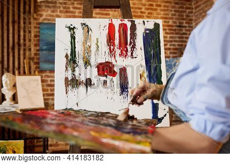 Painter At The Studio Creating Abstract Picture On Canvas Using Oil Paintings And Palette Knife. You