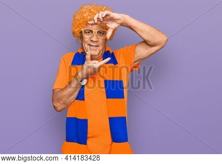 Senior hispanic man football hooligan cheering game smiling making frame with hands and fingers with happy face. creativity and photography concept.