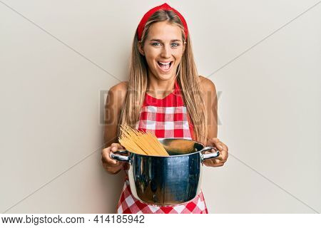 Young blonde woman wearing professional baker apron holding cooking pot with spaghetti smiling and laughing hard out loud because funny crazy joke.