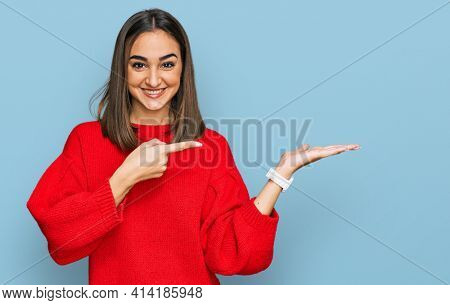Beautiful brunette woman wearing casual winter sweater amazed and smiling to the camera while presenting with hand and pointing with finger.
