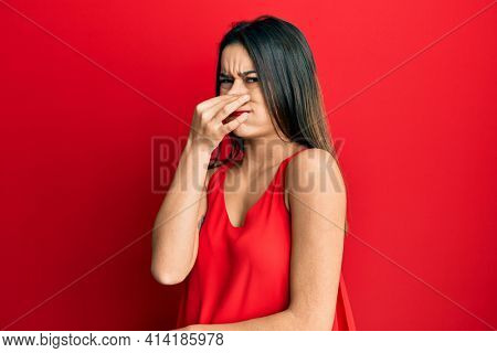 Young hispanic girl wearing casual style with sleeveless shirt smelling something stinky and disgusting, intolerable smell, holding breath with fingers on nose. bad smell