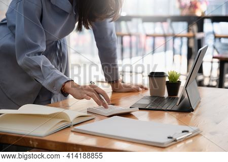 Young Asian Accountant Using Calculations. Savings, Finances, Tax And Economy Concept.