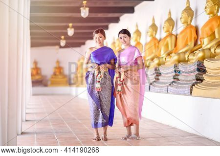 Attractive Thai Women In Traditional Thai Dress Hold Fresh Flower Garlands For Entering A Temple Bas