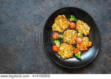 Chopped Chicken Breast And Broccoli Schnitzels On A Black Plate Against A Dark Concrete Background.