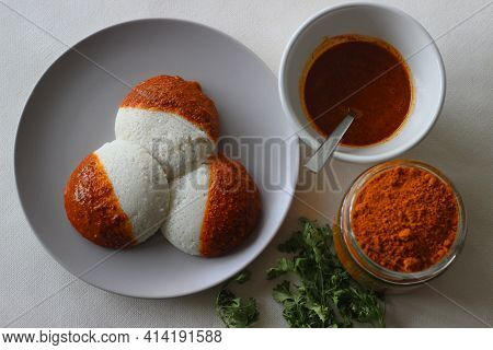 Idli Half Covered With Podi Chutney Also Named As Gunpowder. Podi Is Made Of Ground Pulses, Dried Re