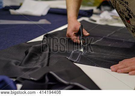 Dressmaker Cutting Dress Fabric On Sketch Line. Fashion Designer Tailor Or Sewer In Workshop Studio