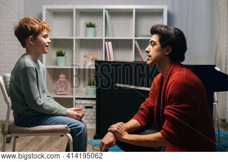 Father Having Conversation With 8-year-old Son By Looking Him In Eye At Home. Loving Parent Dad Of S