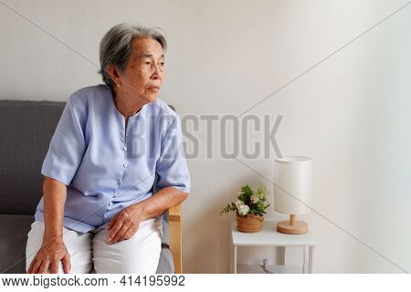 Elderly Asian Woman With Grey Hair Sitting Lonely On The Sofa, Aging Society Sad And Lonely Concept,