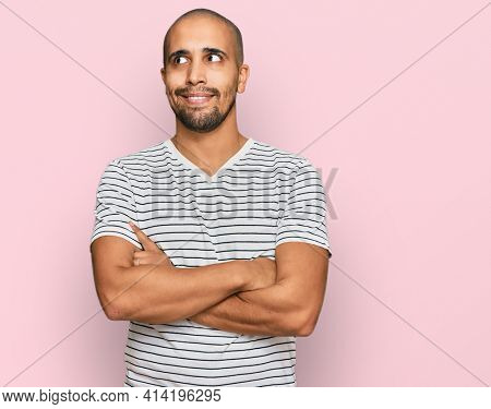 Hispanic adult man wearing casual clothes smiling looking to the side and staring away thinking.