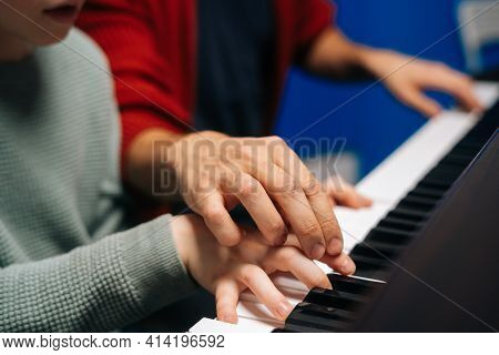 Side Close-up View Fingers Of Child Boy Playing Piano, Music Teacher Sitting Near And Helps With Pla
