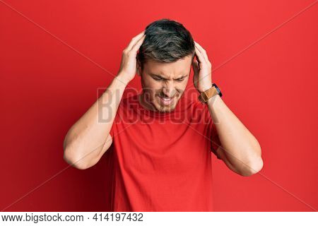 Handsome caucasian man wearing casual red tshirt suffering from headache desperate and stressed because pain and migraine. hands on head.