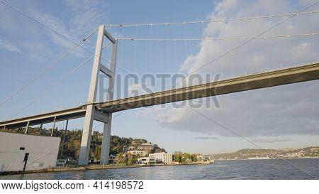 View From Boat Passing Under Bridge. Action. Bottom View Of Suspension Bridge Over Bosphorus. Hangin