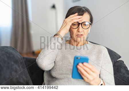 Worried Senior Woman Staring At A Smartphone Screen At Home, Upset Retire Female Lying Down On The C