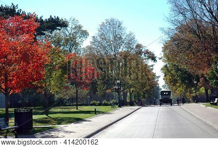DEARBORN, MICHIGAN - SEPT 29, 2006: Old Car driving on tree lined lane at the Henry Ford Museum.