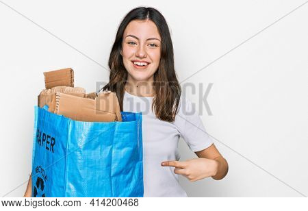 Young beautiful woman holding recycling wastebasket with paper and cardboard smiling happy pointing with hand and finger