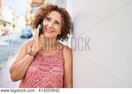 Middle age woman talking on the smartphone leaning on the wall at street of city.