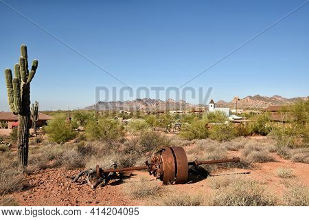 APACHE JUNCTION, ARIZONA - 8 DEC 2016: Mining equipment and cactus at the Superstition Mountain Museum with the Elvis Memorial Chapel in the background, in Apache Junction, Arizona.