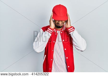 Young african american man wearing baseball uniform with hand on head for pain in head because stress. suffering migraine.
