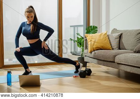Young brunette woman in green jumpsuit does yoga standing in high lunge pose on blue mat by panoramic window and green pot plant