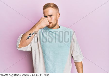Young caucasian man wearing casual clothes smelling something stinky and disgusting, intolerable smell, holding breath with fingers on nose. bad smell