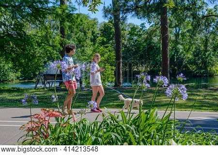 New Orleans, La, Usa - May 3: Young Couple Walking Dog  On The Path In Audubon Park On May 3, 2020 I